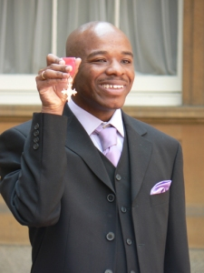 """Stephen Wiltshire holding MBE"" by Original uploader was Stwilts at en.wikipedia - Transferred from en.wikipedia. Licensed under Public Domain via Commons."